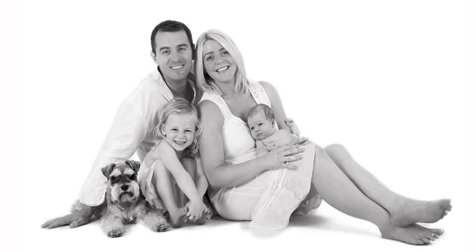 black and white photo family with dog
